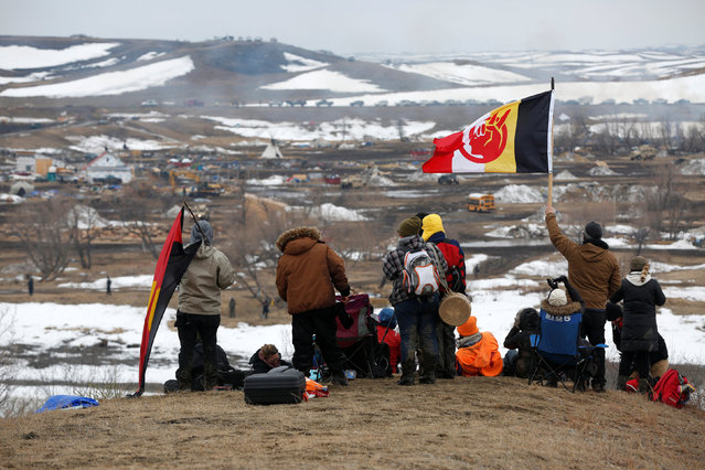 Protesters watch law enforcement officers sweep through the main opposition camp against the Dakota Access oil pipeline near Cannon Ball, North Dakota, U.S., February 23, 2017. (Photo by Terray Sylvester/Reuters)