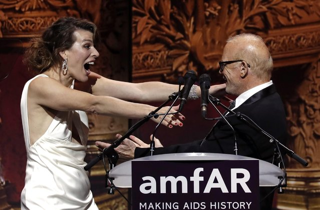 Milla Jovovich and William H. Roedy, Chairman of amfAR during the auction on May 23, 2019 during the amfAR 26th Annual Cinema Against AIDS gala at the Hotel du Cap-Eden-Roc in Cap d'Antibes, southern France, on the sidelines of the 72nd Cannes Film Festival. (Photo by Eric Gaillard/Reuters)