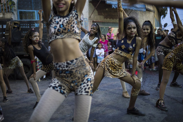 Young dancers from the Style Dance Academy perform during a Mother's Day block party in Caracas, Venezuela, Sunday, May 19, 2019. (Photo by Rodrigo Abd/AP Photo)