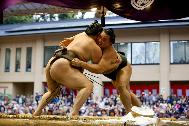 "Mongolian-born grand sumo champions Hakuho (L) and Harumajuji compete during a show fight at the ""Honozumo"", a ceremonial sumo tournament, at the Yasukuni Shrine in Tokyo April 3, 2015. (Photo by Thomas Peter/Reuters)"