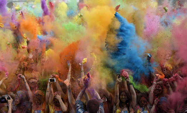 Participants throw up colored powder during the Color Up race in Istanbul, Turkey, 17 May 2015. The event is based on the Hindu Spring festival Holi, also known as the festival of colors where participants color each other with dry powder and colored water. (Photo by Deniz Toprak/EPA)