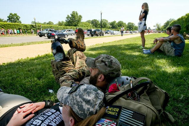 Army Staff Sgt. Earl Granville of Arlington, Va., second from left, and former Army Spc. Jessica Red of Orlando, Fla., left, rest together in the grass outside Arlington National Cemetery in Arlington, Va., Monday, May 25, 2015, on Memorial Day. (Photo by Andrew Harnik/AP Photo)