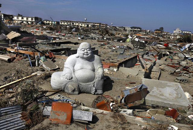 A statue of Hotei Buddha sits in the debris in the  tsunami-destroyed town of Sendai, Miyagi Prefecture, northern Japan Friday, April 1, 2011. (Photo by Vincent Yu/AP Photo)