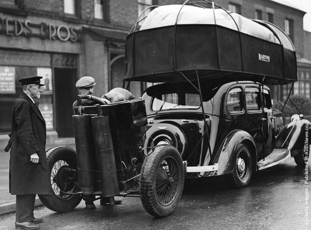 1930: A car driven by gas held in a large balloon on the roof and pulling a gas trailer