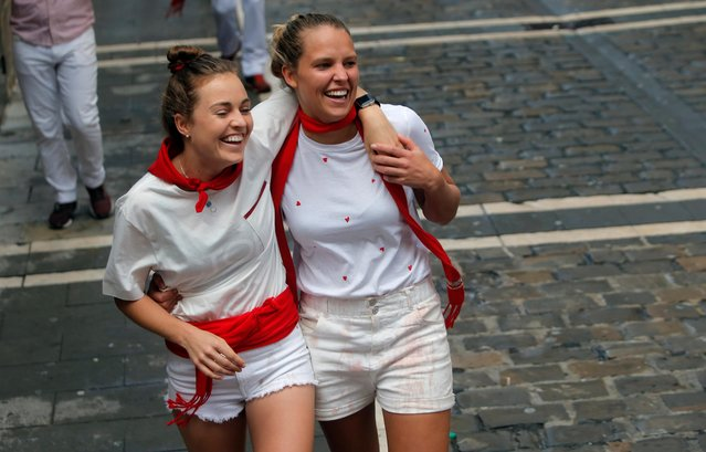 Revellers react after taking part in the second running of the bulls at the San Fermin festival in Pamplona, Spain, July 8, 2019. (Photo by Jon Nazca/Reuters)