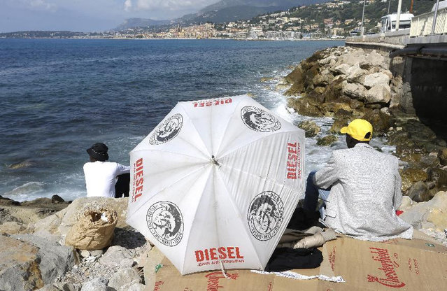Migrants look at France side as they are blocked at the Franco-Italian border near Menton, southeastern France, Tuesday, June 16, 2015. Some 150 migrants, principally from Eritrea and Sudan, have been trying since last Friday to cross the border from Italy but have been blocked by French and Italian police. (AP Photo/Lionel Cironneau)