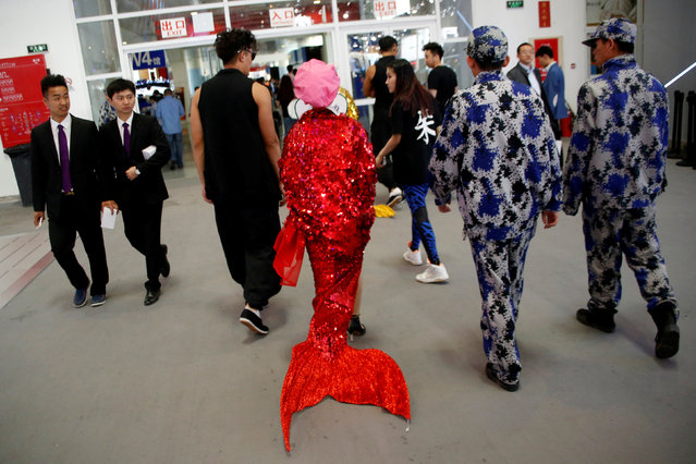 A woman dressed in a mermaid costume makes her way during the Auto China 2016 show in Beijing, China April 26, 2016. (Photo by Kim Kyung-Hoon/Reuters)