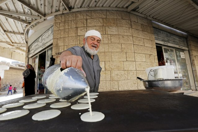 A man makes traditional sweets in a market during the holy month of Ramadan in the town of Ramtha, Jordan, June 25, 2015. (Photo by Muhammad Hamed/Reuters)