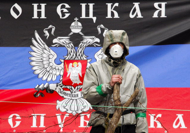 A pro-Russian militiaman guards a barricade in front of the flag of so called Donetsk Republic outside a regional police building in eastern Ukrainian city of Slavyansk on April 14, 2014. Ukraine's latest ultimatum to pro-Kremlin militias who have seized buildings across a swath of the separatist east expired on Monday without any sign of the gunmen ready to give in. (Photo by Anatoliy Stepanov/AFP Photo)