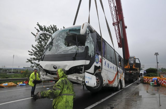 A bus is lifted by a crane after a traffic accident on a highway in Wuhu, Anhui province, China, June 26, 2015. At least 12 people were killed after the bus clashed with a truck and overturned on Friday, local media reported. (Photo by Reuters/Stringer)