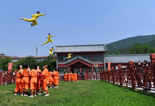 Shaolin students perform martial arts or kungfu on the rooftop of a building during a general assembly to celebrate the 70th anniversary of the founding of the People's Republic of China on the Songshan Mountain (Mount Songshan or Song Mountain) in Dengfeng city, Zhengzhou city, central China's Henan province, 13 July 2019. (Photo by Li Jianan/Xinhua News Agency/Barcroft Media)