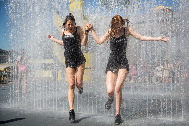 People cool off in a fountain outside the Southbank Centre on June 30, 2015 in London, England. The UK is currently experiencing a heatwave, with temperatures of 35 degree celsius forecast tomorrow in some parts of the country. The extreme heat has already seen train cancellations and a health warning has been issued. (Photo by Rob Stothard/Getty Images)