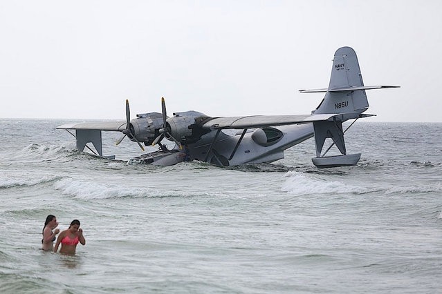 """In this June 30, 2015 photo, a vintage PBY-6A flying boat rests on the sandy bottom of the Gulf of Mexico, just off the shore near Orange Beach, Ala. The aircraft took on water and became stranded while it was being used in the filming of the Nicolas Cage movie """"USS Indianapolis: Men of Courage"""". (Photo by Brian Kelly/Al.com via AP Photo)"""