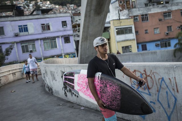 """Cristiano Gomes """"Xuxu"""" leaves Rocinha slum on his way to Sao Conrado beach in Rio de Janeiro, Brazil, Thursday, May 21, 2015. Before he learned how to surf at the school, his """"life was pretty bad"""", he says. He would juggle for spare change from motorists at the busy highway intersection at the base of the Rocinha shantytown. (Photo by Felipe Dana/AP Photo)"""
