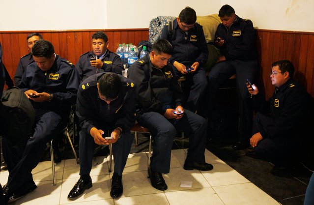 Air Force members check their cell phones after protesting for a second day, as they rest at the headquarters of the National Association of Warrant Officers and Sergeants in La Paz, Bolivia, Wednesday, April 23, 2014. Hundreds of low ranking soldiers from Bolivia's Armed Forces marched for a second day against the military high command's dismissal of four of its leaders who defended their call for more career opportunities. (Photo by Juan Karita/AP Photo)