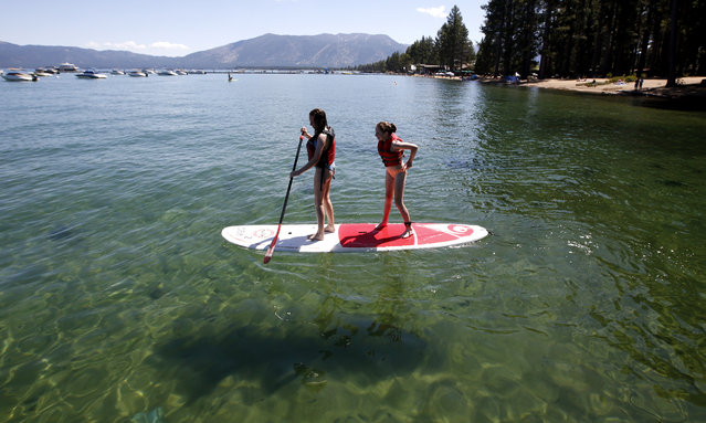 Freya Mayo, 15, left and her sister Evie, 13, of London, England, try out a paddle board on the clear waters of Lake Tahoe near the site of the 23rd annual Lake Tahoe Summit, at South Lake Tahoe, Calif., Tuesday, August 20, 2019. The summit is a gathering of federal, state and local leaders to discuss the restoration and sustainability of Lake Tahoe. (Photo by Rich Pedroncelli/AP Photo)