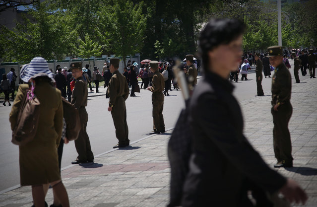 North Korean soldiers stand by a sidewalk while people carrying decorative flowers make their way from the Kim Il Sung Square Sunday, May 8, 2016, in Pyongyang, North Korea. (Photo by Wong Maye-E/AP Photo)