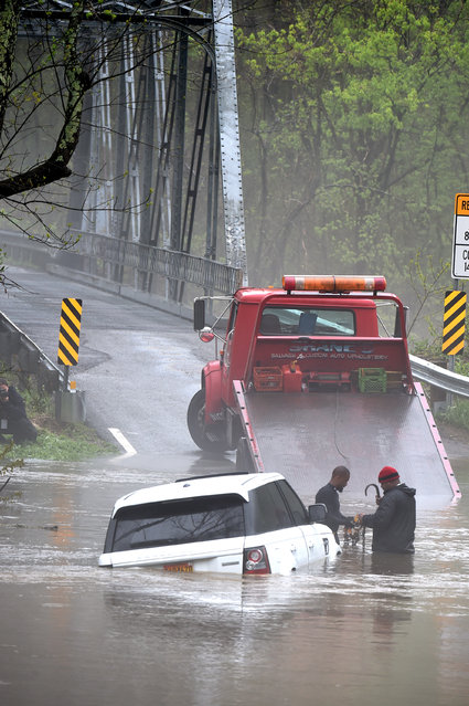 Tow truck operators Frank Cole (L) and Rick Commock of Blaze towing Co. stand in the floodwaters on Governors Bridge road to tow out a 2013 Land Rover as a massive storm system drops heavy rains on the DC region with cold temperatures and winds on April 30,  2014 in Bowie, MD. (Photo by Jonathan Newton/The Washington Post)