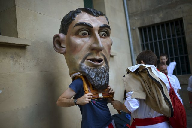 "Kilikis help each other dress during San Fermin festival's ""Comparsa de gigantes y cabezudos"" (Parade of the Giants and Big Heads) in Pamplona, northern Spain, July 8, 2015. (Photo by Vincent West/Reuters)"