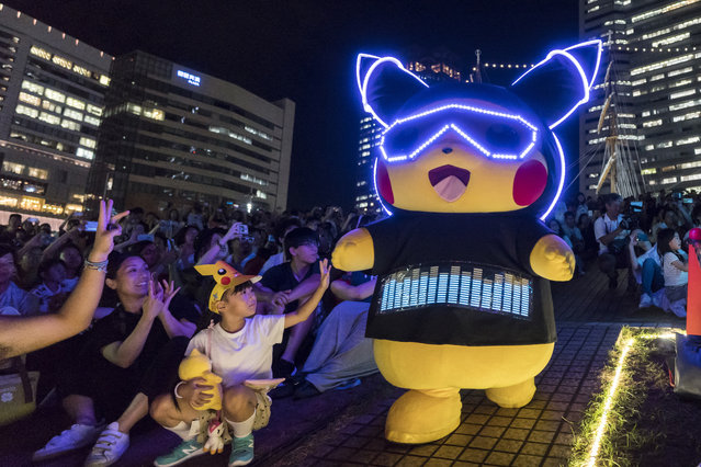 A performer dressed as Pikachu, a character from the Pokémon media franchise managed by The Pokémon Company, marches during the Pikachu Outbreak event at night on August 8, 2019 in Yokohama, Japan. A total of 2,000 Pikachus appear at the city's landmarks in the Minato Mirai area aiming to attract visitors and tourists to the city. The event will be held through August 12. (Photo by Tomohiro Ohsumi/Getty Images)