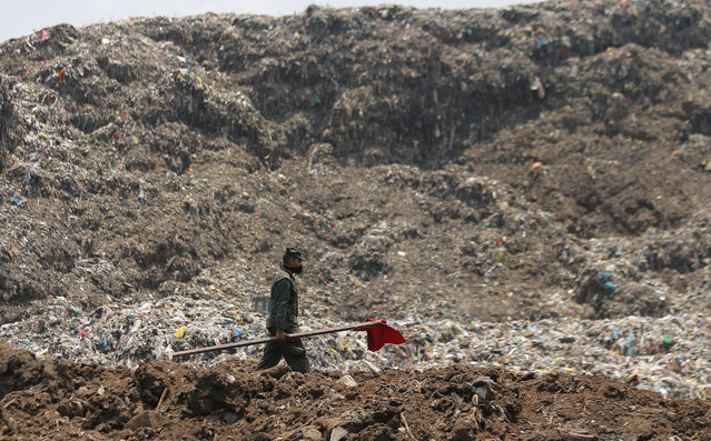 A Sri Lankan army soldier walks to erect red flags to demarcate danger zones following the collapse of a garbage mound in Meetotamulla, on the outskirts of Colombo, Sri Lanka, Colombo, Sri Lanka, Monday, April 17, 2017. Rescuers on Monday were digging through heaps of mud and trash that collapsed onto a clutch of homes near a garbage dump outside Sri Lanka's capital, killing dozens and possibly burying dozens more. (Photo by Eranga Jayawardena/AP Photo)