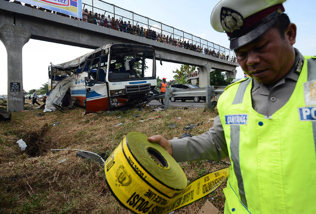 A member of the Indonesian police forces cordons off the wreck of a bus shortly after it crashed into a steel bar on a toll road in Cirebon, Indonesia, July 14, 2015. According top local reports the bus was carrying more than 40 passengers, mostly Muslims travelling to celebrate  Eid al-Fitri hit the steel bar killing 12 and wounding dozens. (Photo by EPA/Stringer)