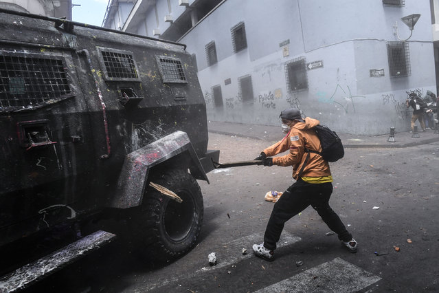 A demonstrator hits a riot police vehicle with a stick during clashes in Quito, as thousands march against Ecuadorean President Lenin Moreno's decision to slash fuel subsidies, on October 9, 2019. (Photo by Martin Bernetti/AFP Photo)