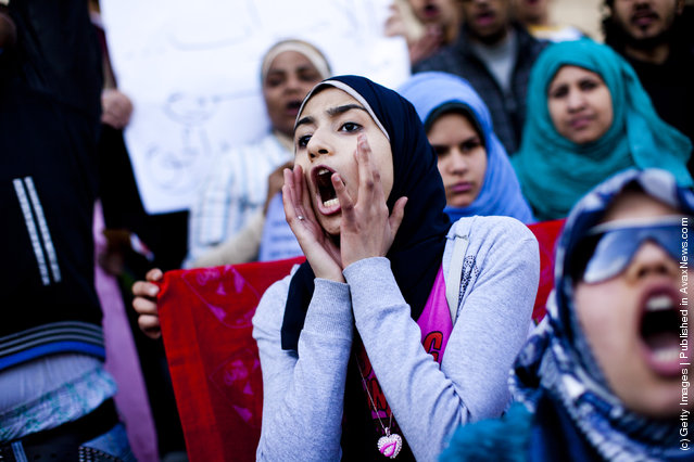 Female students shout slogans in front of the Cairo University during a protest against the military rulers of the country
