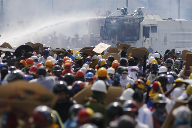 The water canon sprays anti-government protesters as security forces block an opposition march in Caracas, Venezuela, Wednesday, May 10, 2017. (Photo by Ariana Cubillos/AP Photo)