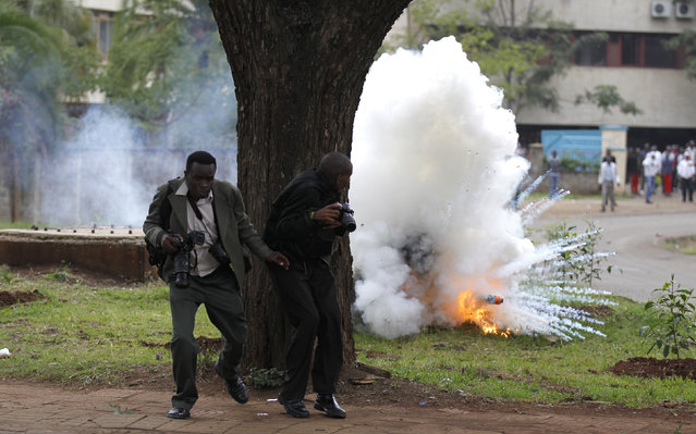 Photojournalists run away from a flare after police released teargas in a bid to disperse rioting university students in Kenya's capital Nairobi May 20, 2014. Public university students started their protests, which are against the planned hiking of fees and lowering of maximum loan awarded to students by the Higher Education Loans Board, where police engaged the students in running battles at the main campus, local media reported. (Photo by Thomas Mukoya/Reuters)