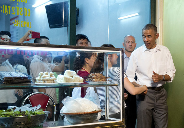 President Barack Obama greets women at the door as he walks from the Bún chả Hương Liên restaurant after having dinner with American Chef Anthony Bourdain in Hanoi, Vietnam, Monday, May 23, 2016. (Photo by Carolyn Kaster/AP Photo)