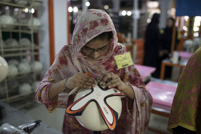 An employee adjusts outer panels of a soccer ball inside the soccer ball factory that produces official match balls for the 2014 World Cup in Brazil, in Sialkot, Punjab province May 16, 2014. (Photo by Sara Farid/Reuters)