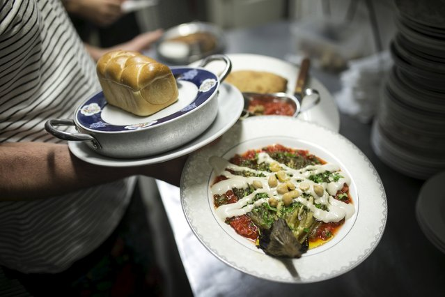 A waiter carries plates of food at Georgian restaurant Nanuchka in Tel Aviv, Israel July 15, 2015. Nana Shrier, owner of Nanuchka, shocked Israel's culinary world when she removed all animal-based products from the menu. Nanuchka is part of a growing trend that has transformed Israel's financial center into a haven for meatless cuisine. (Photo by Baz Ratner/Reuters)