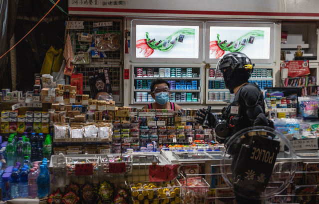 A police officer speaks with a street vendor during a dispersal operation in Hong Kong, China on November 2, 2019. Pro-democracy protesters once again took to the streets in their latest battle against the government. Despite the full withdrawal of the extradition bill, the initial catalyst of unrest, protesters continue to reemphasize that the remaining 4 demands must be met. Protesters clashed violently with police, resulting in numerous injuries and arrests. (Photo by Aidan Marzo/SOPA Images/Rex Features/Shutterstock)