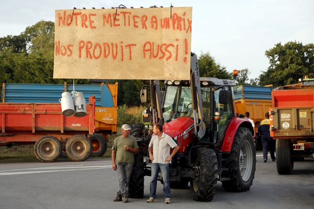 "Livestock breeders block the entrance to the Saint Brice-en-Cogles milk house in the northwestern region of France, to protest against a squeeze in margins by retailers and food processors, July 21, 2015. The banner read ""Our job has a price – Our products also!"". (Photo by Jacky Naegelen/Reuters)"