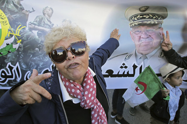 An Algerian woman gestures by a poster showing Algeria's army chief Gen.Ahmed Gaid Salah during a march against EU interference into Algeria's policy, Saturday, November 30, 2019 in Algiers after the European Parliament on Thursday condemned the grim reality of human rights in Algeria. The march was a show of support for the government and Algeria's army chief Gen.Ahmed Gaid Salah. (Photo by Toufik Doudou/AP Photo)