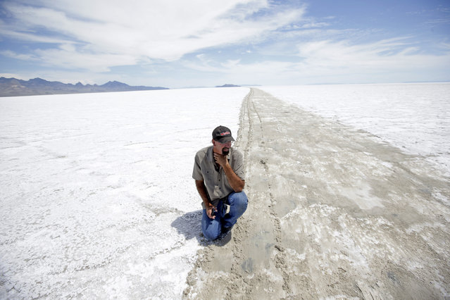 In this Tuesday, July 21, 2015, photo, Wendover Mayor Mike Crawford kneels down along the exposed mud track on the Bonneville Salt Flats, in Utah. Crawford, who owns an auto parts shop in town, said the decision by race organizers to cancel this year's event weeks away will be a bigger economic blow than last year, when a monsoon storm left standing water on the track on the eve of the race. Wet weather has forced the second-straight cancellation of an annual race at Utah's world-famous Bonneville Salt Flats. (Photo by Rick Bowmer/AP Photo)