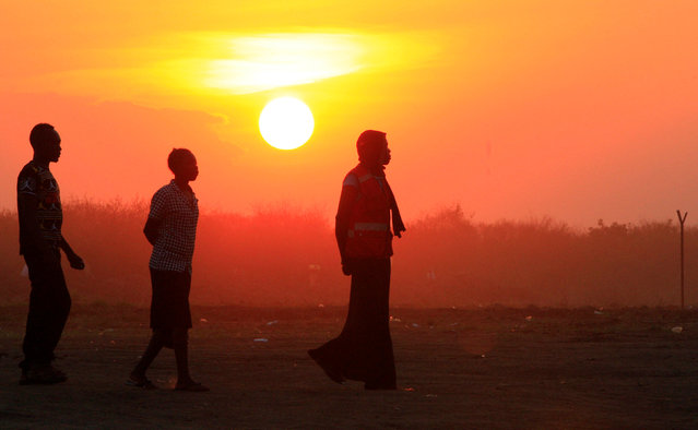 People who fled fighting in South Sudan are seen walking at sunset on arrival at Bidi Bidi refugee's resettlement camp near the border with South Sudan, in Yumbe district, northern Uganda December 7, 2016. (Photo by James Akena/Reuters)