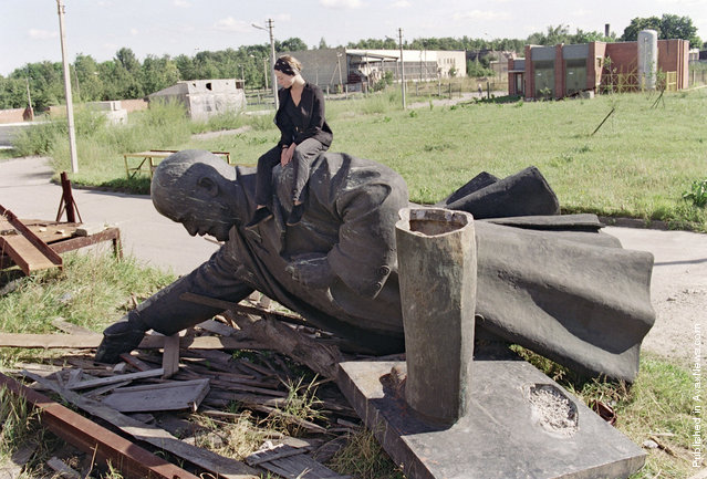 A young Lithuanian girl sits on the toppled statue of Russian Bolshevik revolutionary leader Vladimir Lenin in Vilnius after the monument was removed from the center of the Lithuanian capital, on September 1, 1991