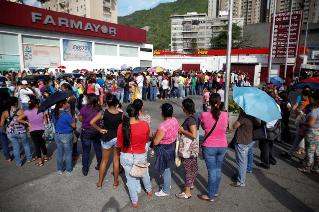 People line up to try to buy toilet paper and diapers outside a pharmacy in Caracas, Venezuela May 16, 2016. (Photo by Carlos Garcia Rawlins/Reuters)