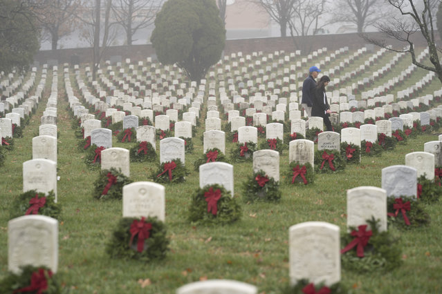 People walk among headstones with holiday wreaths in Arlington National Cemetery during Wreaths Across America Day in Arlington, Va., Saturday, December 14, 2019. Maine businessman Morrill Worcester started the annual event in 1992 at Arlington National Cemetery, and it has expanded to hundreds of veterans' cemeteries and other locations in all 50 states and overseas. (Photo by Sait Serkan Gurbuz/AP Photo)
