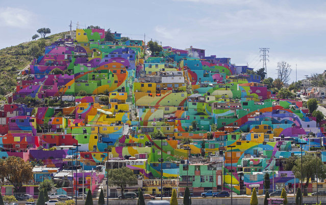 Hundreds of houses painted in bright colors in what organizers claim is Mexico's largest mural, is part of a government-sponsored project is called Pachuca Paints Itself, in the Palmitas neighborhood, in Pachuca, Mexico, Thursday, July 30, 2015. German Crew is the artist collective responsible for painting the mural project. Director Enrique Gomez, who goes by MYBE, said the crew has painted 1,500 square meters with 20,000 liters of paint. (Photo by Sofia Jaramillo/AP Photo)