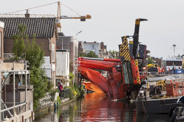 Two collapsed cranes are seen in Alphen aan de Rijn, the Netherlands August 3, 2015. Two cranes hoisting a massive section of bridge collapsed in a western Dutch town on Monday, flattening a row of houses and injuring at least 20 people, authorities said. (Photo by Ronald Fleurbaaij/Reuters)