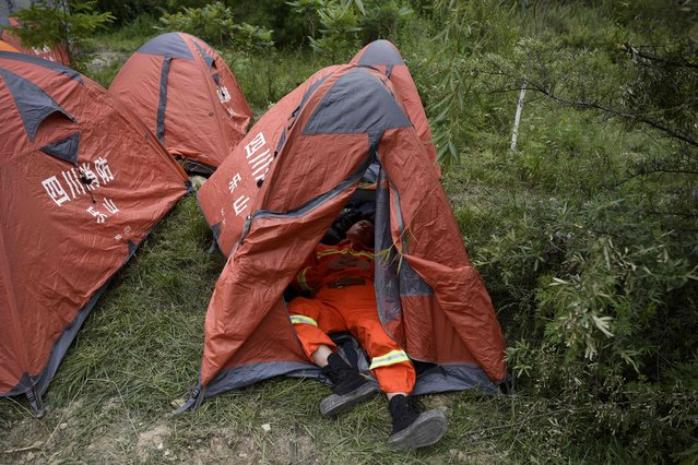 A rescue worker takes a rest in a tent near  landslide area in the village of Xinmo in Maoxian county, China's Sichuan province on June 24, 2017. (Photo by Wang Zhao/AFP Photo)