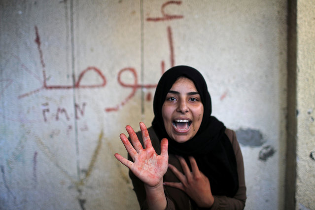 The sister of Palestinian militant Emad Naseer, who was killed in an Israeli air strike, reacts with her hand stained with his blood, during his funeral in the northern Gaza Strip on May 4, 2019. (Photo by Mohammed Salem/Reuters)