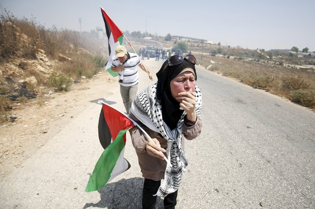 Palestinian protesters holding Palestinian flags react to tear gas fired by Israeli troops during clashes at a protest against Jewish settlements in the West Bank village of Nabi Saleh, near Ramallah August 7, 2015. (Photo by Mohamad Torokman/Reuters)