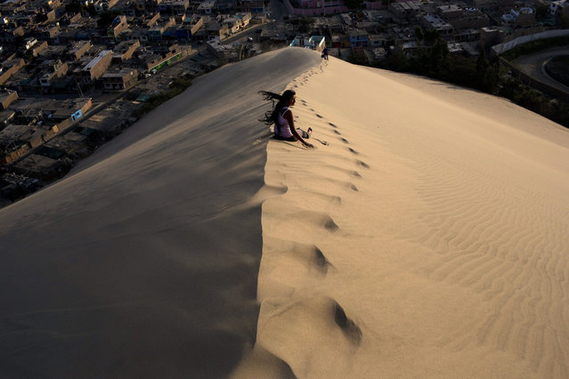 A woman waits for a friend while climbing the Cerro de Saraja, a mountain of sand, in Ica, Peru, Friday, August 7, 2015. (Photo by Rodrigo Abd/AP Photo)