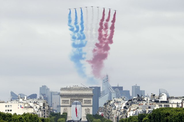 Nine alphajets of the French Air Force Patrouille de France release trails of blue, white and red smoke, the colors of French national flag, as they fly over the Champs-Elysees avenue during the annual Bastille Day military parade in Paris, on July 14, 2014. (Photo by Thomas Samson/AFP Photo)