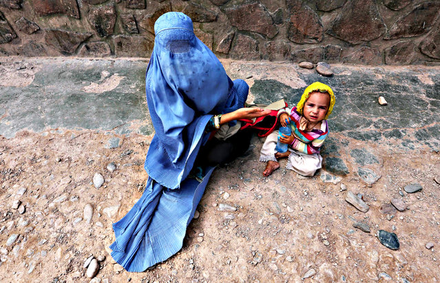An Afghan woman waits to get medical treatment at the refugee camp in Herat, Afghanistan, 03 August 2015. The camp provides refugees with basic medical treatment, education, food and hygiene. (Photo by Jalil Rezayee/EPA)