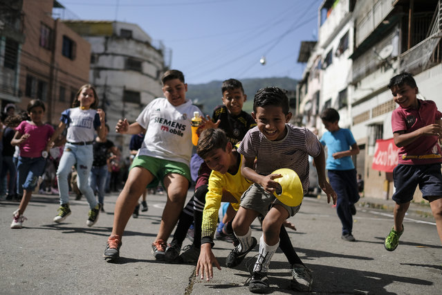 In this July 20, 2019 photo, children play during a sports event organized by members of the Caracas FC soccer club, in Catia, one of the poorest slums in Caracas, Venezuela. When the Caracas Football Club plays, its supporters leave their ideological preferences and socioeconomic differences behind, joining together to support and take care of each other inside and outside the stadium. (Photo by Matias Delacroix/AP Photo)